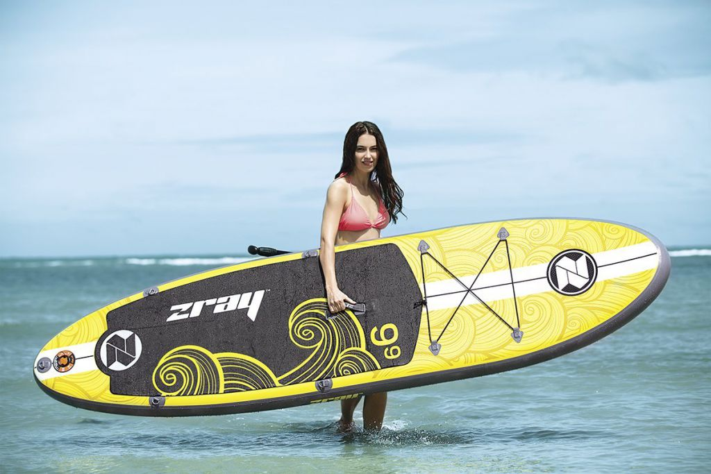 z-ray x1 inflatable stand up paddle board being carried by a woman